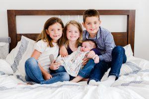 Kids holding newborn baby