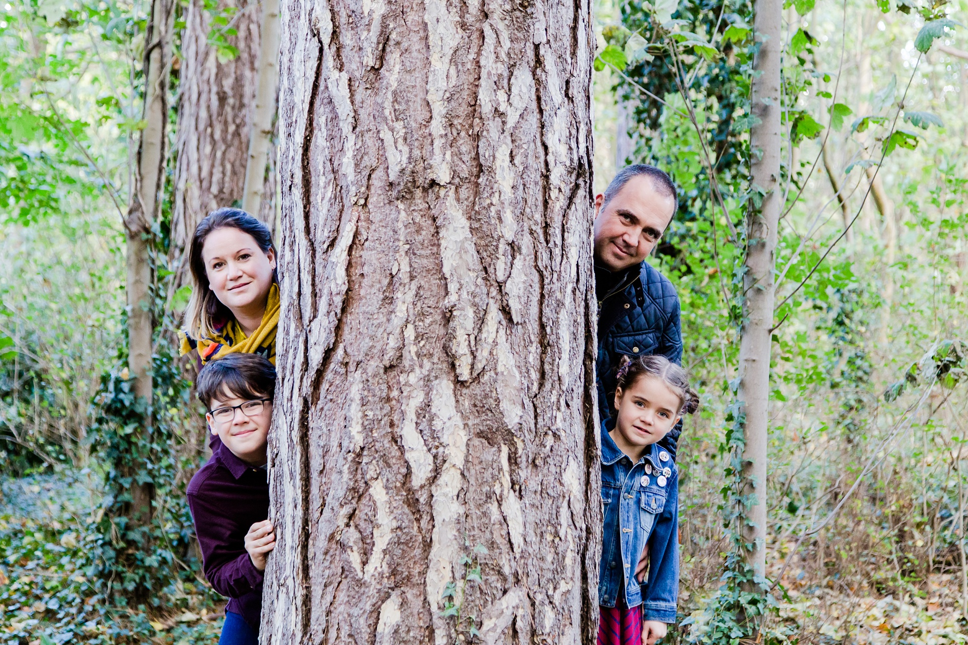 Family photo shoot hiding behind tree