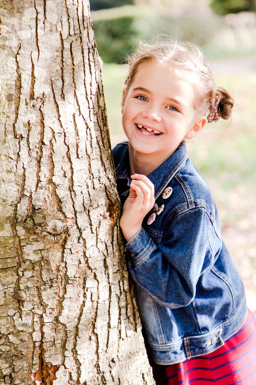 Girl hiding behind tree in park